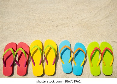 Four pairs of beach sandals on white sand