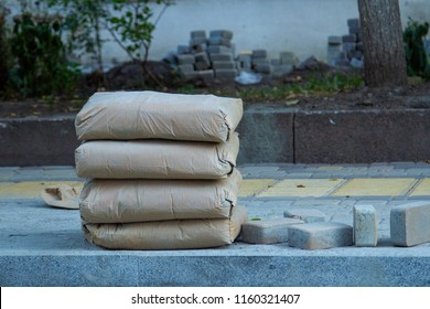 Four Paper bags with cement are stacked on the sidewalk. Building materials for the construction of sidewalk and footpaths. Cement in paper bags for the construction of pedestrian paths.