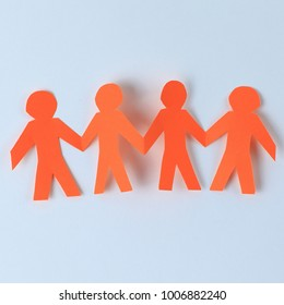 four paper men taking each other's hands