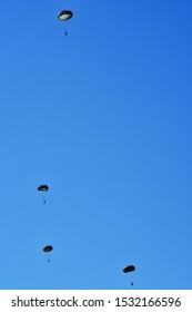 Four of paratrooper descend through the sky