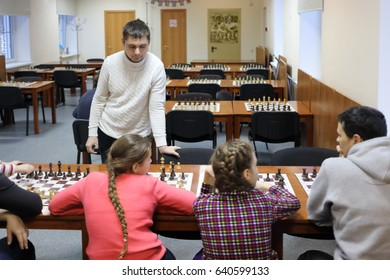 Four people (adults and children) play chess on table in chess club