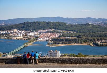 Four people back view on Viana de Castelo landmark, Portugal. Tourists on panoramic landscape background. Viana de Castelo landmark with bridge top view. Landscape of Camino de Santiago. Family travel