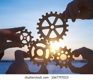 four people businessman hold gears puzzle on sunset background. coherence in work, business concept idea, cooperation, teamwork, strategy.