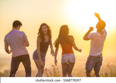 The four people dancing on the bright sun background