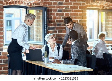 Four people dressed in stylish office clothes discuss task while sit at table. Window open. Behind sits colleague at table