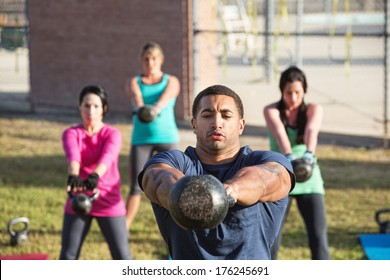 Four people exercising in outdoor boot camp with kettle bells