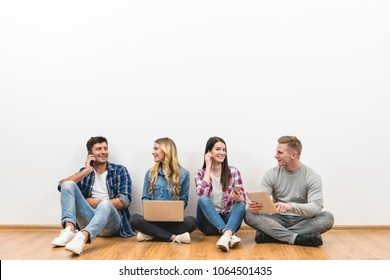 The four people with gadgets sit on the floor on the white wall background