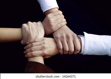 a four people handshake outdoors on black