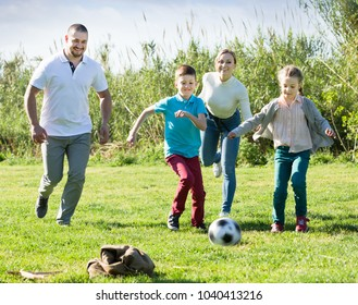 Family of four people happily playing in football and  laughing together outdoors
