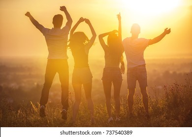 The four people jumping on the sunset background