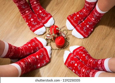 Four people legs wearing red socks with Christmas ornament placed around candles on the floor