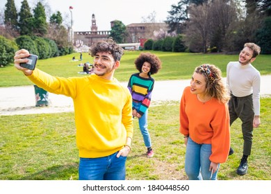 Four people multiethnic friends diverse having fun outdoor using smartphone taking selfie being 6 feet distant respecting social distancing