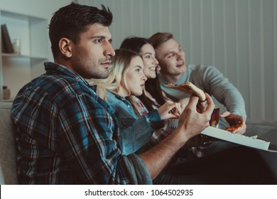 The four people with a pizza watch a movie on the sofa