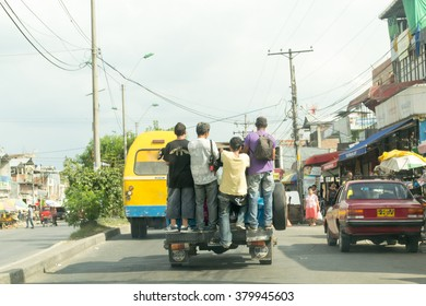 Four people riding on the back of pickup in Cali, Colombia