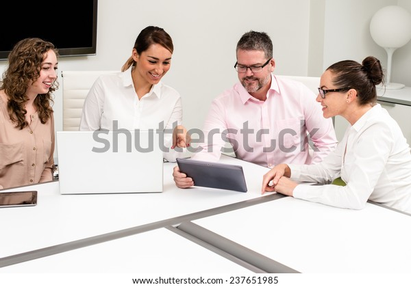 Four people sitting at a conference table having a business meeting.