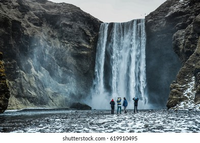 Four people standing in front of big and famous Iceland waterfall Skogafoss