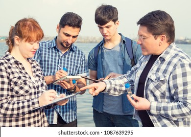 Four people study the problems of ecology, environmental pollution. A group of students are an ecologist and a teacher.