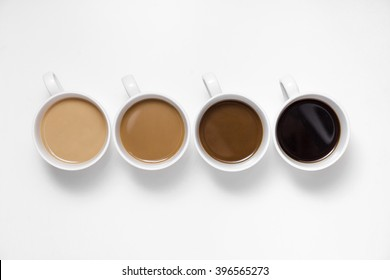 Four perfect white coffee cups with milk and steam isolated on white. Morning concept.