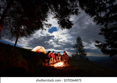 Four person tourists are sitting around a campfire with a beer near the camping and forest at night in the mountains. Blue sky is visible through the clouds. In the distance illuminated orange tent