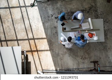Four persons professional team of engineers talk together to review material in construction site, taken from high angle, top view photo with shadow of window frame on floor.