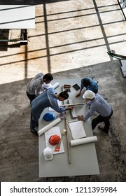Four persons professional team of engineers talk together to review material in construction site, taken from high angle with shadow of window frame on floor.