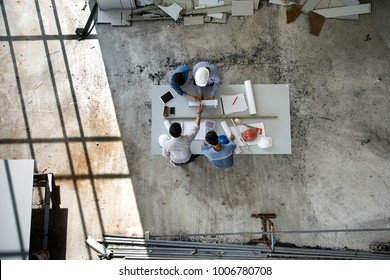 Four persons team of engineers talk together to review constuction material, taken from high angle, top view photo