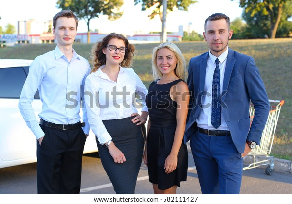 Four perspective modern young people, students, entrepreneurs, two boys and two girls smiling and posing for camera outdoors. One of guys dressed in blue classic suit, white shirt with tie, second man