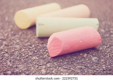 Four pieces of colorful sidewalk chalk on pavement, with selective focus on the pink chalk./Sidewalk chalk
