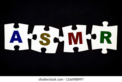 Four pieces of puzzle with letters ASMR on black background. Close-up.