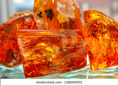 Four pieces of transparent red yellow amber on the background of the waves. Sunstone. Ancient petrified resin. Amber background. Natural mineral crystal for jewelry. Amber with inclusions. Amber light