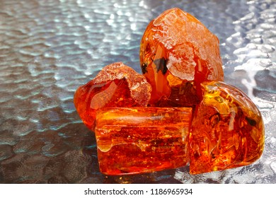 Four pieces of transparent red yellow amber against the background of the waves. Sunstone. Ancient petrified resin. Fashionable decoration. Natural mineral crystal for jewelry. Amber with inclusions
