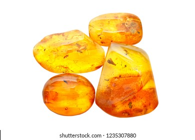 Four pieces of transparent yellow polished amber on a white background. Amber with inclusions. Fossil ancient petrified resin of trees. Sunstone. Natural crystal mineral for jewelry.