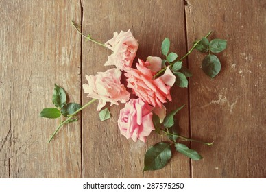 Four pink roses on the rustic wooden table, shot from above. Image filtered in faded, washed out, retro style; nostalgic, romantic vintage concept. Flowers.
