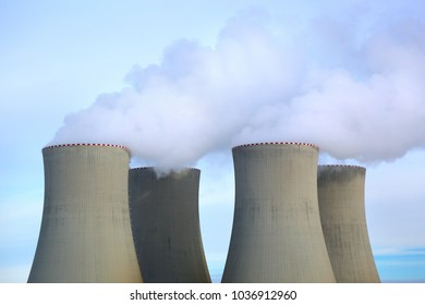 Four pipes of chemical production from which goes white smoke against the blue sky.