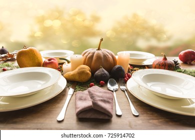 Four plates with cutlery and autumnal vegetables on wooden table