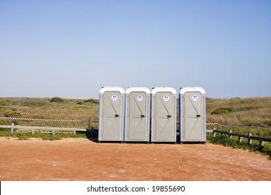 Four portable toilets in gravel parking lot - landscape exterior