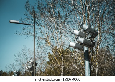 Four powerful spotlights directed upwards as a part of landscape lighting equipment installation outdoors to illuminate big objects at night; bare trees, streetlight and more spotlight poles behind
