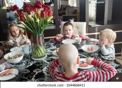 Four preschool kids, boys and girl eating sausages and drink juice sitting at party. Happy children twins and girl eating healthy organic and vegan food at home.
