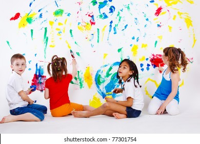 Four preschool kids painting the wall