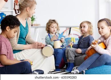 Four preschoolers having fun in kindergarten playing the instruments