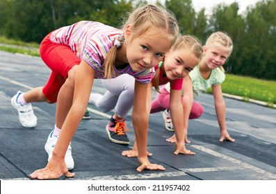 four pre-teen girls starting to run on track