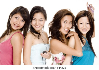 Four pretty young women listening to music on their mp3 players
