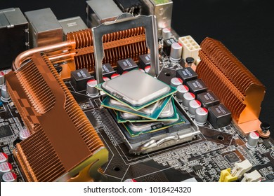 Four processors lie on top of each other in the form of a fan in the socket of the motherboard with orange radiators on the black desk. Progress in the field of IT technologies