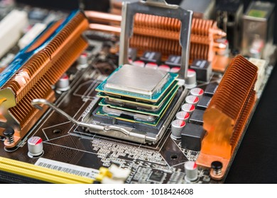 Four processors in an old and dusty game motherboard, lying on top of each other on a black desk. Past computer in new technologies