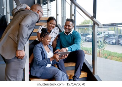 Four professional male and female coworkers sitting on staircase