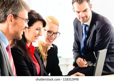 Four professionals in office in business attire looking at laptop screen working together