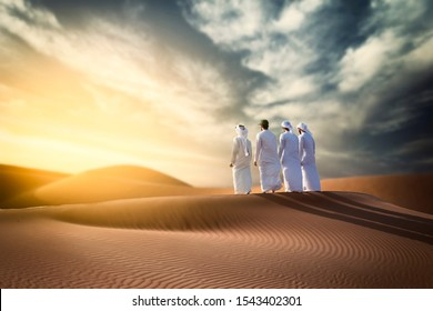 Four Proud Arab Young Man standing on the dune in desert celebrating  spirit of the union - UAE national day