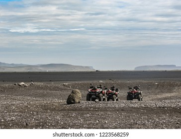 Four quad bikes in Solheimasandur plane wreck place: black sand desert landscape in South Iceland, Europe