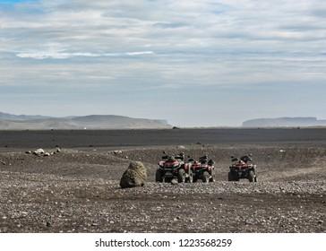 Four quad bikes in Solheimasandur plane wreck place: black sand desert landscape in South Iceland, Europe