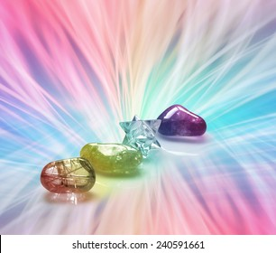 Four Rainbow Healing Crystals on a vibrant radiating rainbow colored energy formation background with plenty of copy space